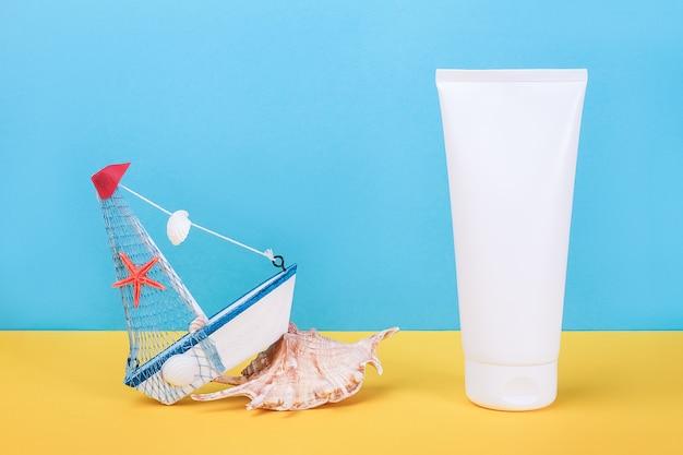 자외선 차단제, 조개 및 소형 보트가있는 흰색 빈 화장품 튜브
