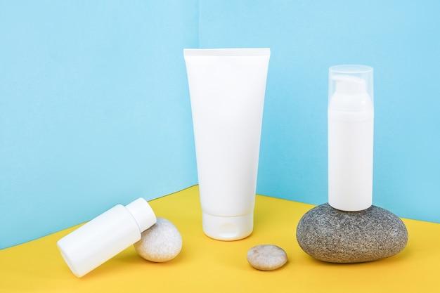 白い空白の化粧品ボトルと黄色の表面に灰色の岩