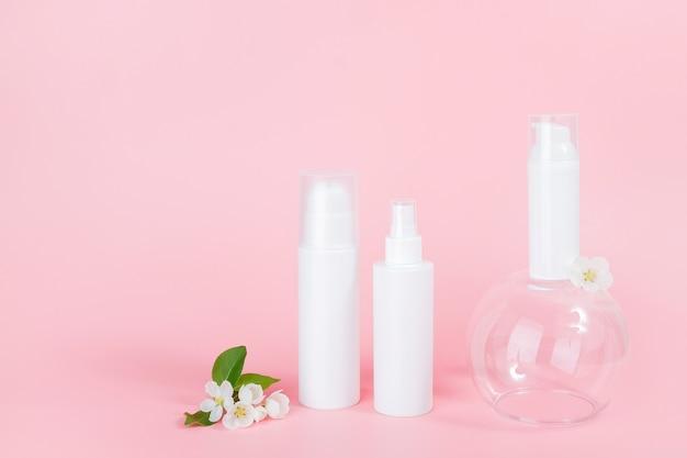 흰색 빈 화장품 병 및 유리 연단 및 꽃 지점에 튜브