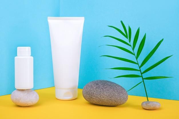 Белые пустые косметические флаконы, тюбик крема, лосьон для тела, лица, рук или другой косметический продукт и серые камни, пальмовый лист на сине-желтом фоне. макет вид спереди, угловая композиция.