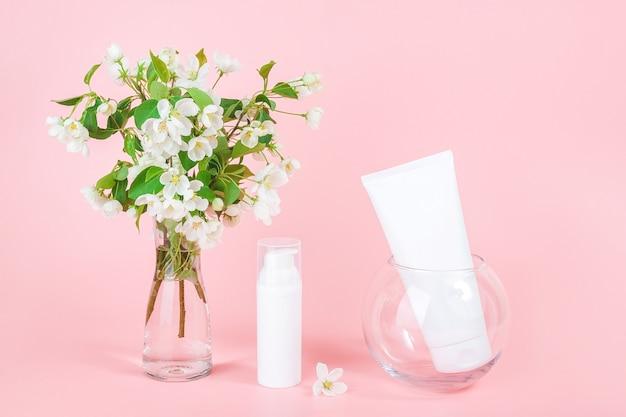 ピンクの花瓶の白い空白の化粧品のチューブとボトルとリンゴの咲く枝