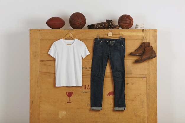 White blank cotton thirt presented near japanese selvedge jeans and leather shoes on wooden big cargo box with vitage playballs on top
