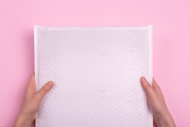 White blank envelope with postal parcel in hands on a pink background. postal industry and cargo delivery.