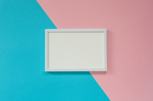 White blank frame on blue and pink  for mockup. flat lay