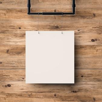 木材の壁の背景にぶら下がっている白い空白のフレーム