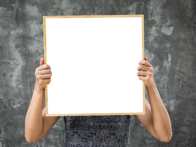 正方形の木製フレームの白い空白のフレームのモックアップ。グランジ灰色のコンクリートの壁の背景に木製フレームで空白の正方形のスペースを保持している女性の手。