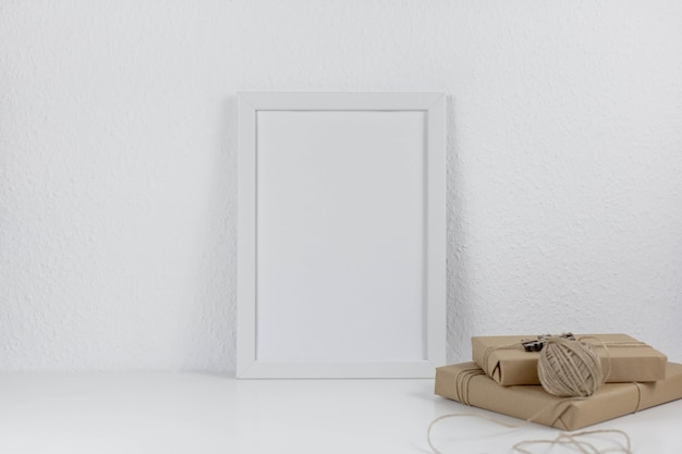 White blank frame mockup with christmas wrapped gifts
