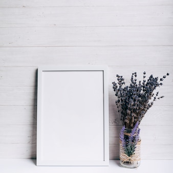 White blank frame near the lavender glass vase on white desk against wooden backdrop
