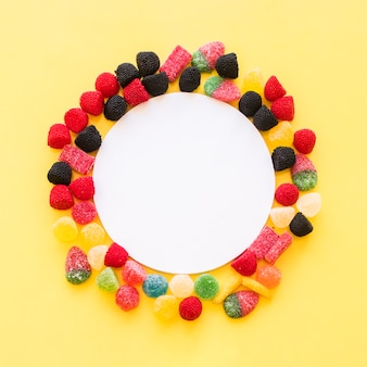 White blank frame surrounded with colorful jelly candies on yellow background