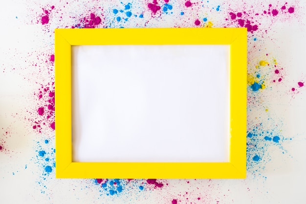 White blank frame with yellow border on holi color powder over white background