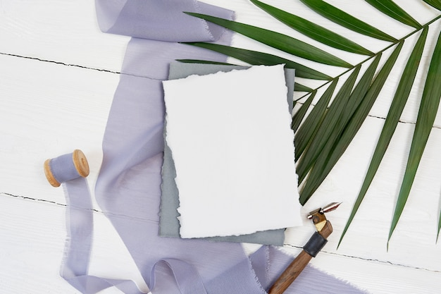 White blank greeting card and grey ribbon with palm leaf and calligraphic pen