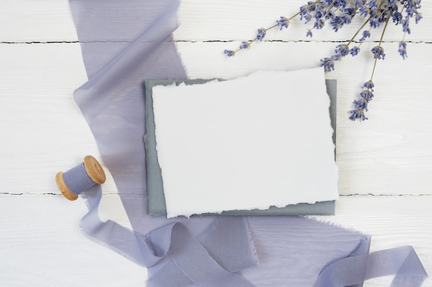 White blank greeting card ribbon on a background of blue fabric
