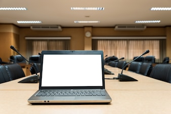 White Blank laptop computer placed on wooden meeting table in empty meeting room.