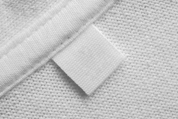 면 셔츠 배경에 흰색 빈 세탁 관리 옷 레이블