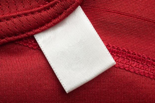 빨간색 폴리 에스터 스포츠 셔츠 배경에 흰색 빈 세탁 케어 의류 라벨