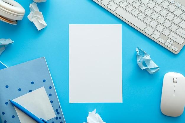 仕事と教育のためのパステルブルーのレイアウトでオフィスと学校の白青の文房具から作られたフレームとコピースペースの白の空白のモックアップ。学校のコンセプトに戻ります。青い机のワークスペース。フラットレイ。