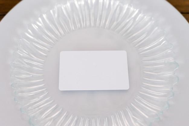 ガラス板上のゲストカードの白い空白のモックアップお祝いの宴会の結婚式を提供しています