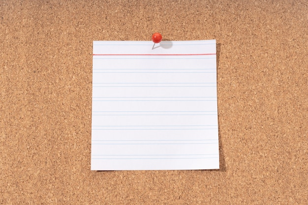 White blank note on a cork board for adding text and push pin