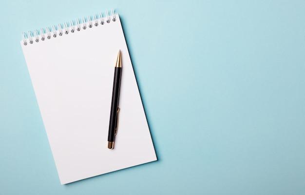 水色の背景に白い空白のノートブックとペン。テキストやイラストを挿入する場所