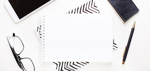 Белый пустой блокнот, очки в черной оправе, телефон и ручка на светлом фоне. разместите для вставки текста или иллюстраций. плоская планировка