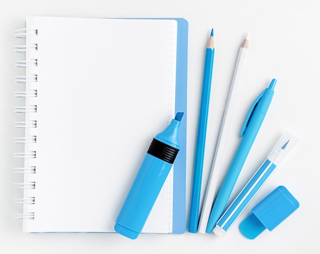 White blank notebook and blue markers with pencils and pen on white. flat lay, mockup.