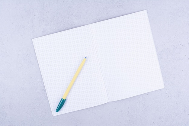 White blank notebook with pens on grey.