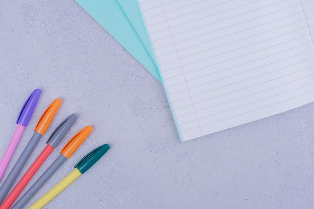 Белый пустой блокнот с ручками на сером.
