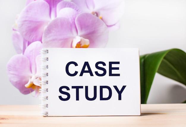 淡いピンクの蘭を背景にテーブルにcasestudyというテキストが書かれた白い空白のノートブック。