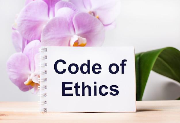 淡いピンクの蘭を背景にテーブルに倫理規定のテキストが付いた白い空白のノートブック。