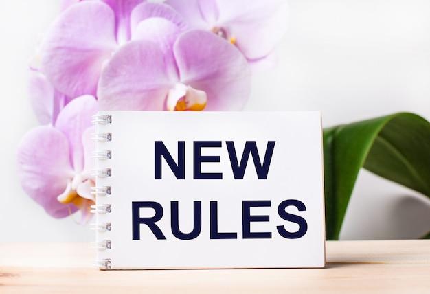 Белый пустой блокнот с текстом новые правила на столе на фоне светло-розовой орхидеи.
