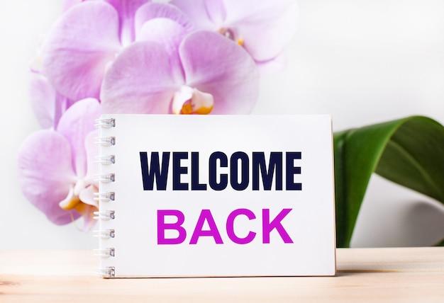 밝은 분홍색 난초의 배경에 대해 테이블에 welcome back이라는 텍스트가 있는 흰색 빈 공책.