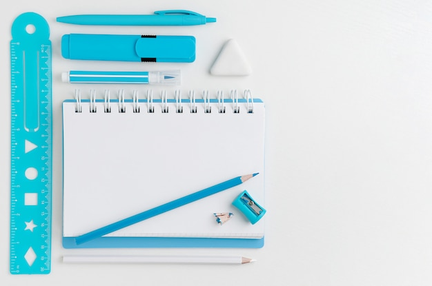 Белые пустые школьные принадлежности блокнота и бирюзы на белом настольном компьютере с космосом экземпляра. вид сверху.