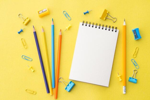 鉛筆とオフィス用品の白い空白のメモ帳、黄色、フラットレイアウト