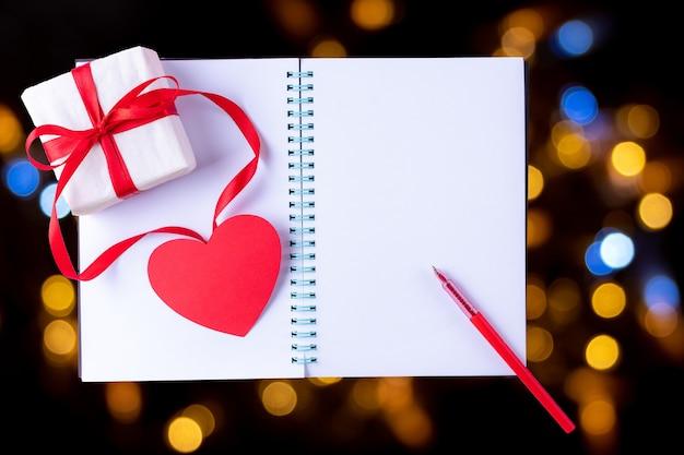 Белая пустая открытая тетрадь, красная ручка, подарочная коробка с красной лентой и сердечко из розовой бумаги