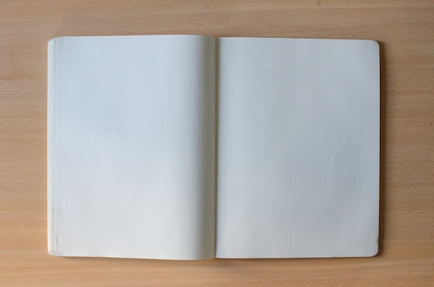 White blank opened copybook with a lot of space of text on a wooden background
