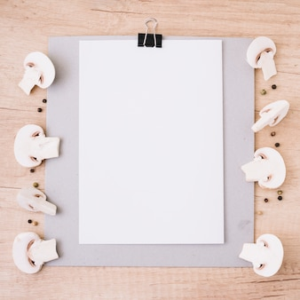 White blank paper attach on clipboard decorated with halved mushrooms and black pepper against wooden textured backdrop