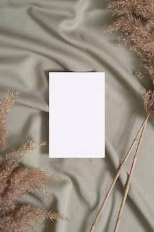 Макет белой пустой бумажной карты с сухой травой пампасов на зеленой ткани нейтрального цвета