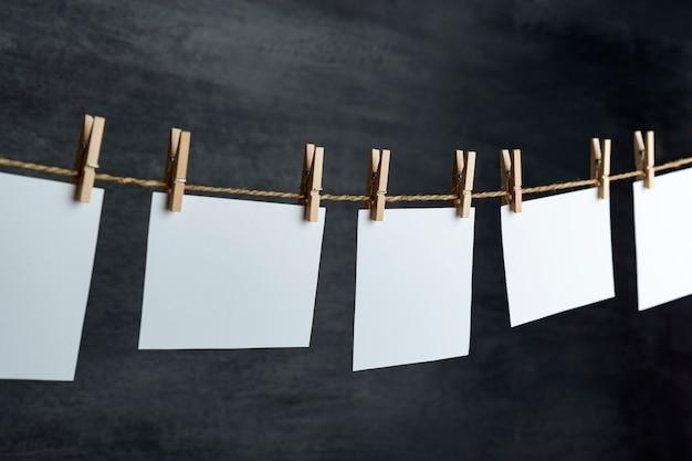 白い白紙のカードは、黒い背景のロープに洗濯バサミでぶら下がっています。スペースをコピーします。あなたのテキストのための場所。