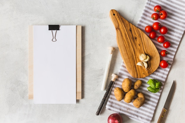 White blank paper on clipboard with vegetables and spices on white texture background