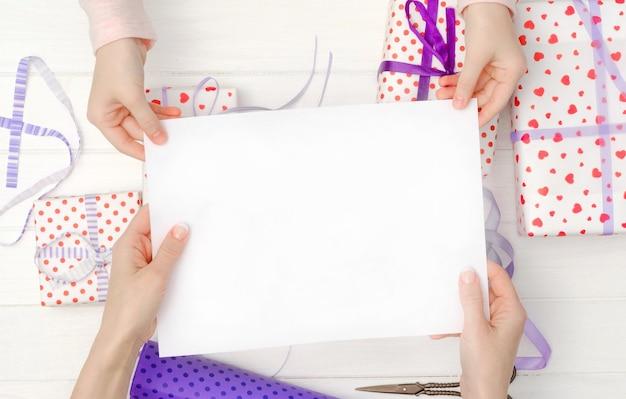 手とギフトの休日のコンセプトに白い空白の紙