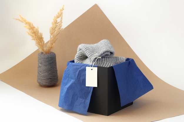 White blank paper logo tag on a grey knitted scarf in a black box and blue tissue paper and dried pampas grass in a spool yarn vase on beige paper