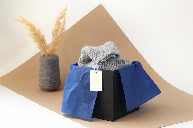 Белая пустая бумажная бирка с логотипом на сером вязаном шарфе в черной коробке и синей папиросной бумаге и сушеной пампасной траве в вазе с катушкой пряжи на бежевой бумаге