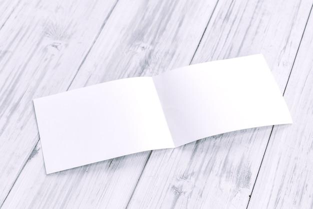 木製のテーブル上に白い空の紙誌のモックアップ