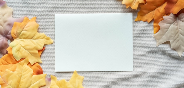 White blank paper page with group of dried orange color maple leaves on ripple fabric background
