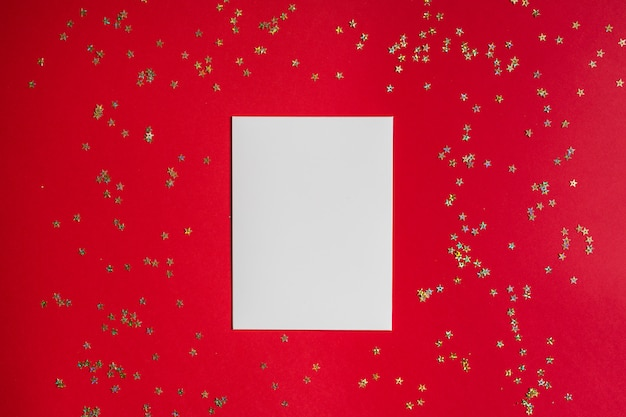 White blank paper on red background with golden confetti