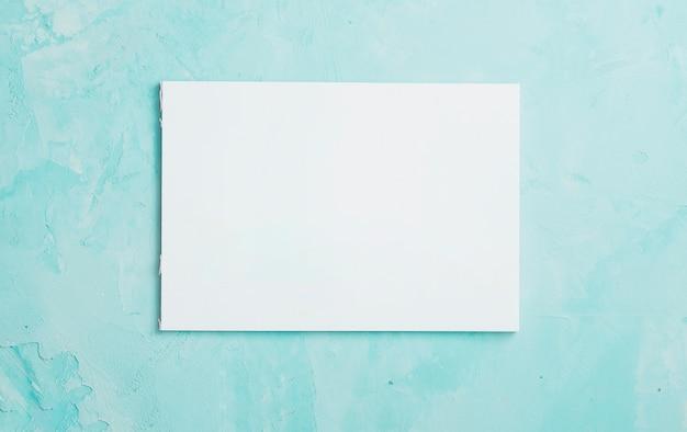 青い織り目加工の表面上の白い空白の紙のシート