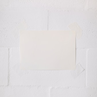 White blank paper stick with tape on white wall backdrop