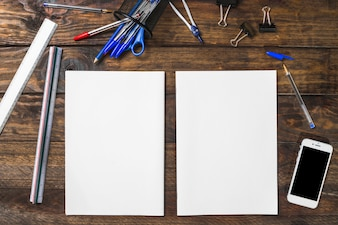 White blank paper surrounded with stationeries and smartphone on wooden table