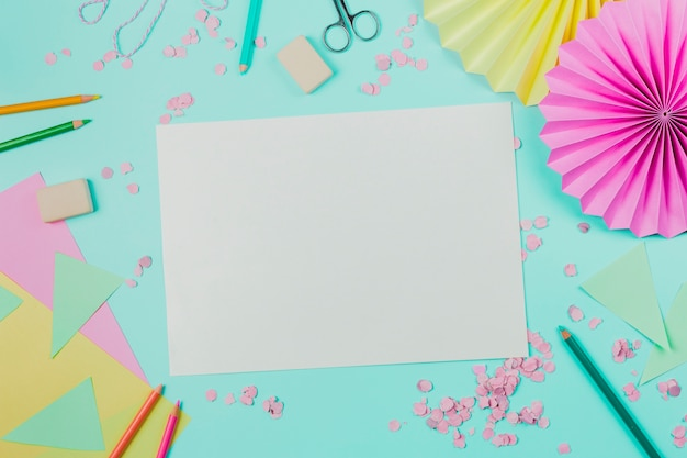 White blank paper with confetti; colored pencils; scissor and eraser on turquoise backdrop