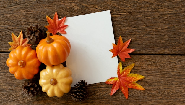 White blank paper with group of pumpkins , pinecone and maple leaves on vintage brown wood table